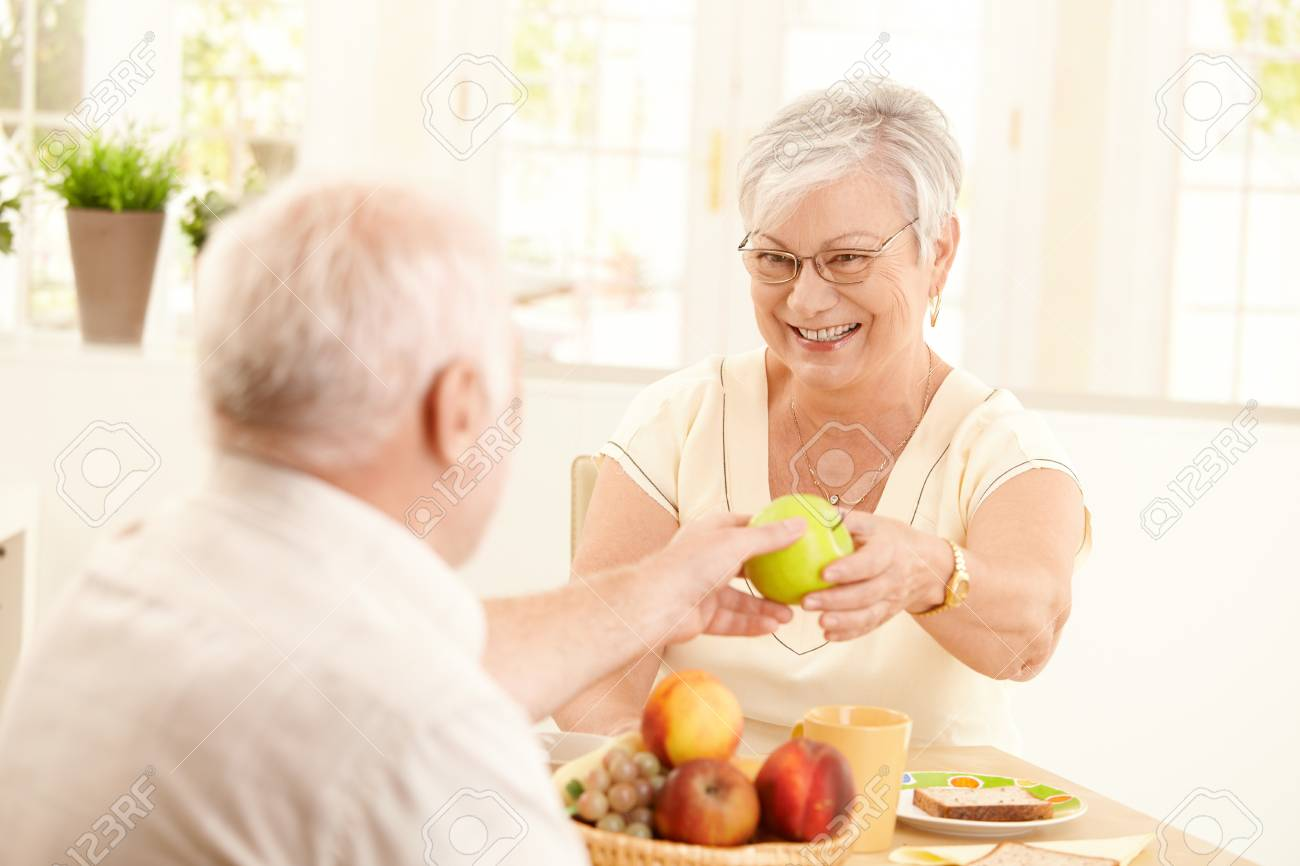 Laughing senior wife getting green apple from husband, sitting at kitchen table, having breakfast. Stock Photo - 8250780