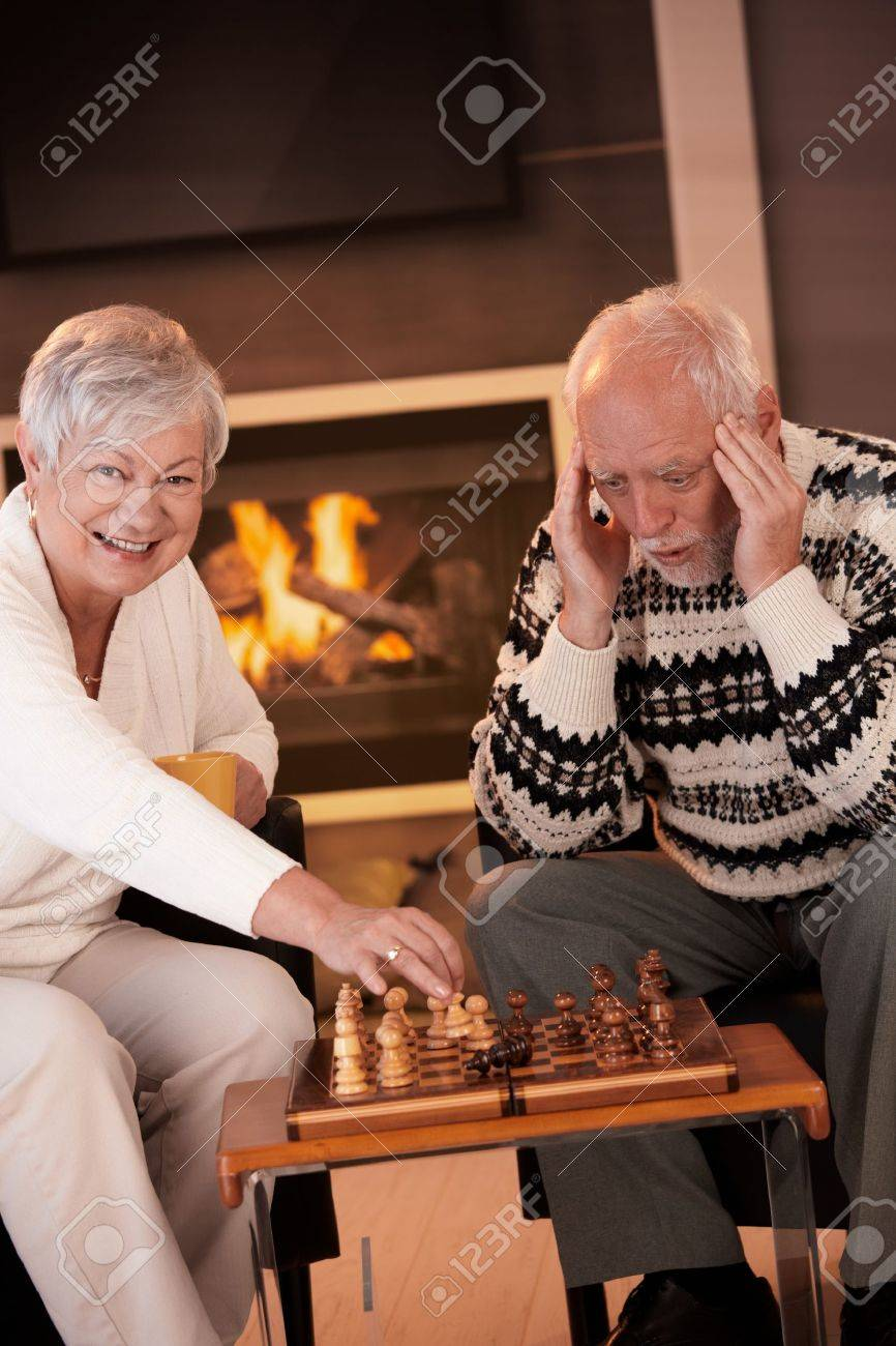 Couple playing chess in cosy living room in front of fireplace, elderly woman winning the game, senior man looking troubled. Stock Photo - 8250903