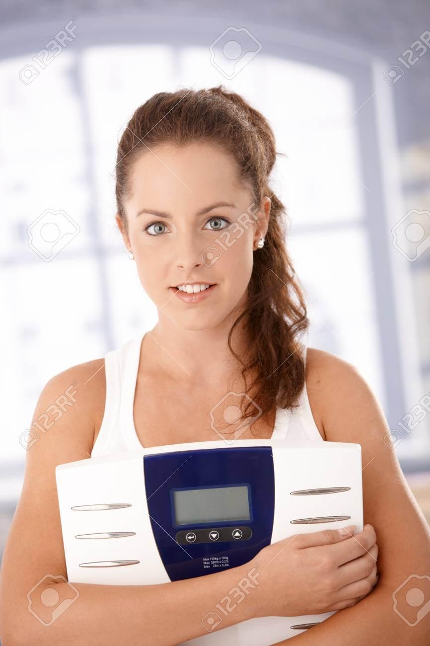 Pretty girl holding scale in hands, smiling, dieting. Stock Photo - 8251194