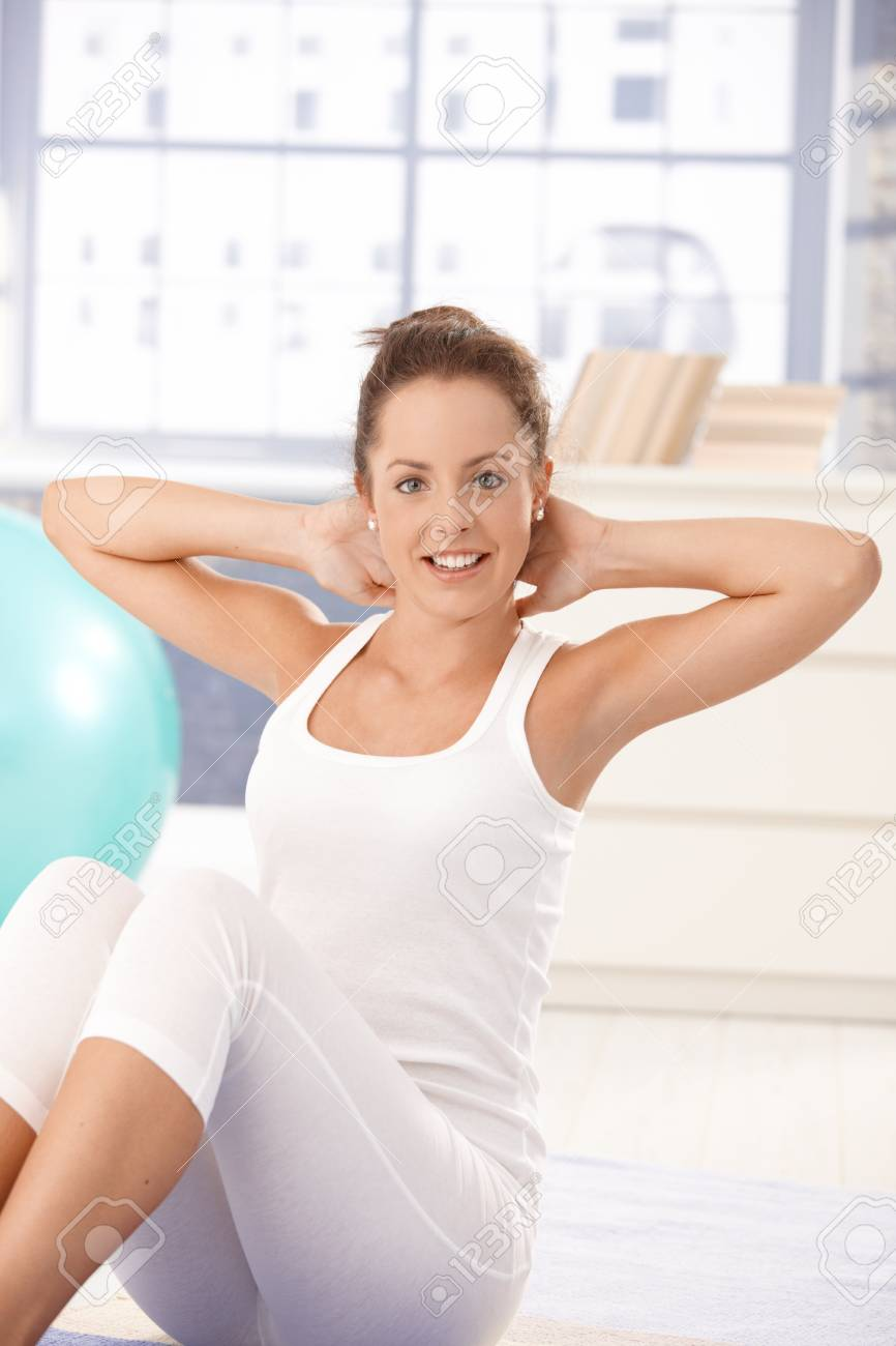 Pretty young girl doing exercises on floor at home, smiling. Stock Photo - 8251021
