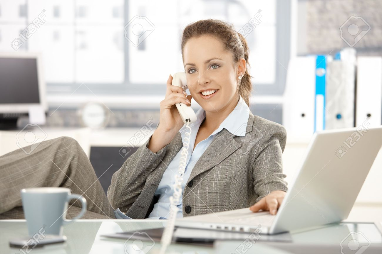 Attractive businesswoman sitting at desk, talking on phone, having laptop, smiling. Stock Photo - 8251350