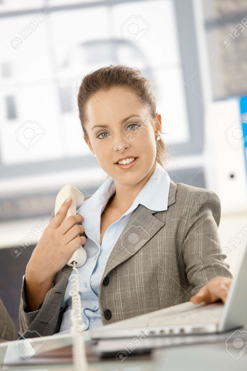 Attractive businesswoman sitting at desk in office, holding phone, having laptop, smiling. Stock Photo - 8251356
