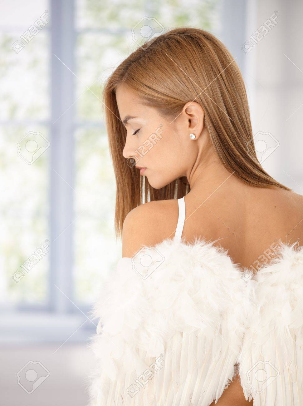 Attractive girl front of window with angel wings viewed from back, eyes closed. Stock Photo - 8398030