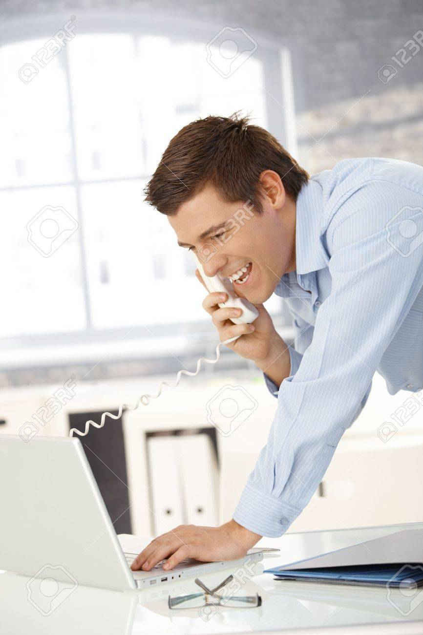 Laughing professional man on landline call with laptop computer, looking at screen. Stock Photo - 8398111