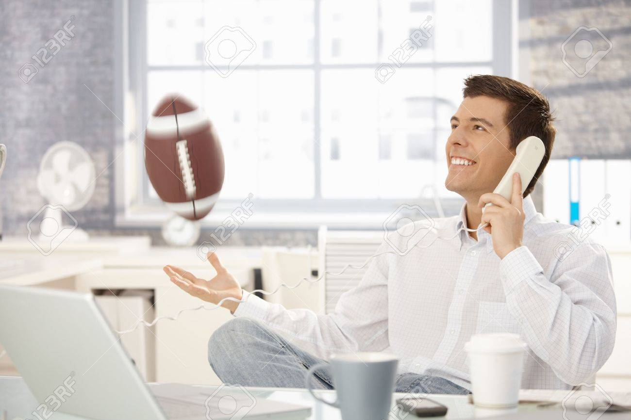 Businessman playing with football office while on landline call, laughing. Stock Photo - 8398110