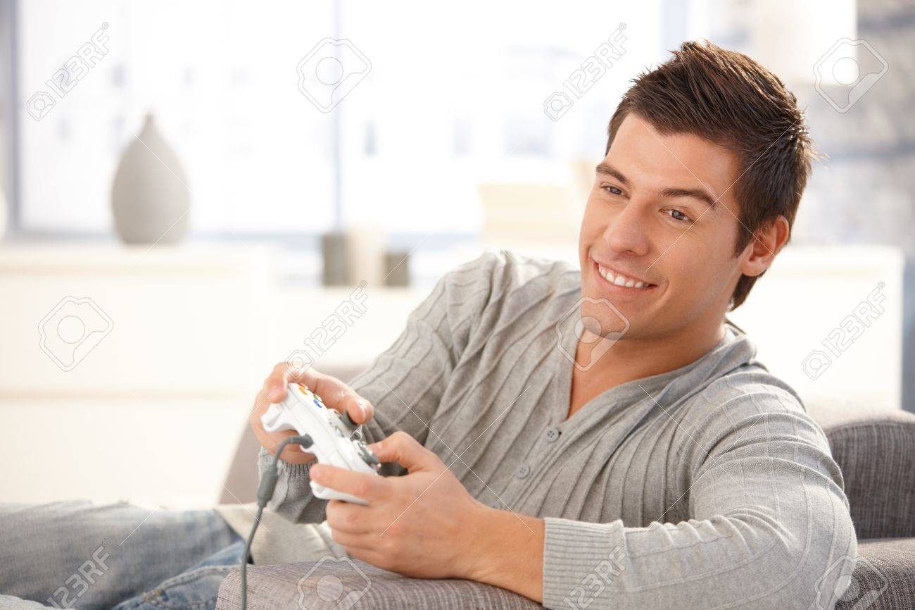 Young guy enjoying computer game, playing with joystick, smiling happily. Stock Photo - 8398131