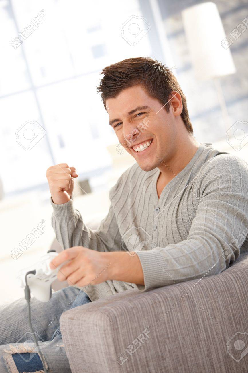 Young man happy about winning in computer game at home, raising fist in triumph. Stock Photo - 8398156