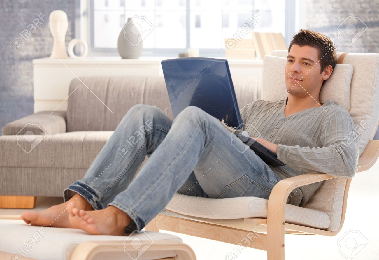 Goodlooking young man relaxing at home in armchair, sitting in living room with laptop computer, smiling. Stock Photo - 8398164