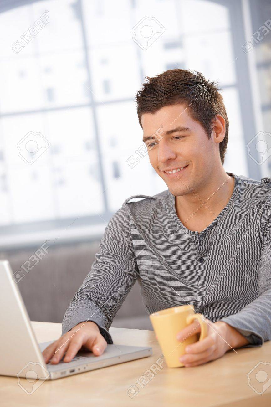 Smiling guy using laptop computer, looking at screen, having coffee at desk. Stock Photo - 8398186
