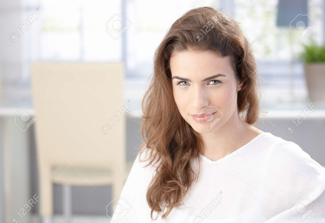 Attractive young female smiling at home in white. Stock Photo - 8534621