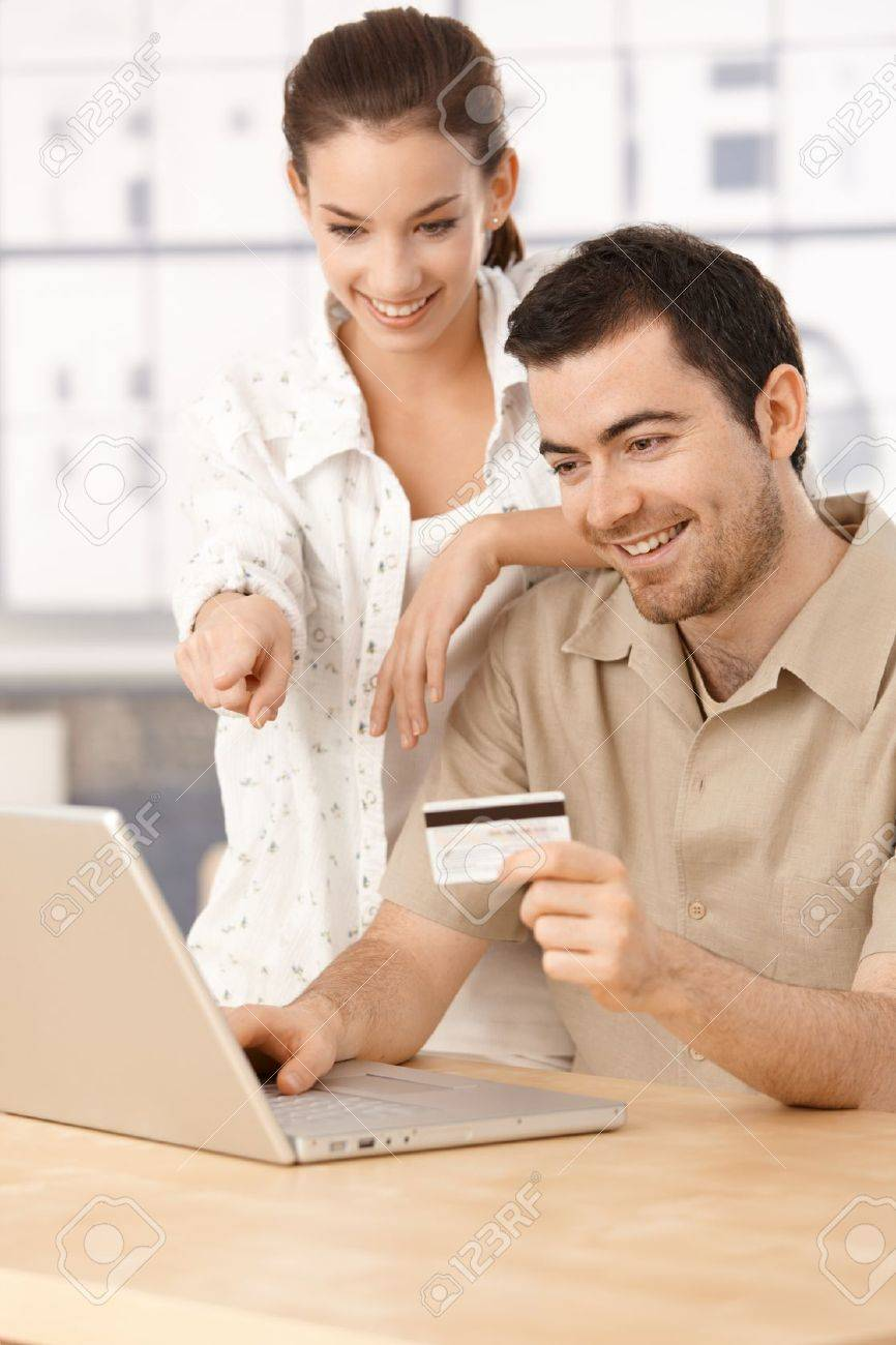 Happy couple using laptop, shopping online at home, using credit card, having fun. Stock Photo - 8552012
