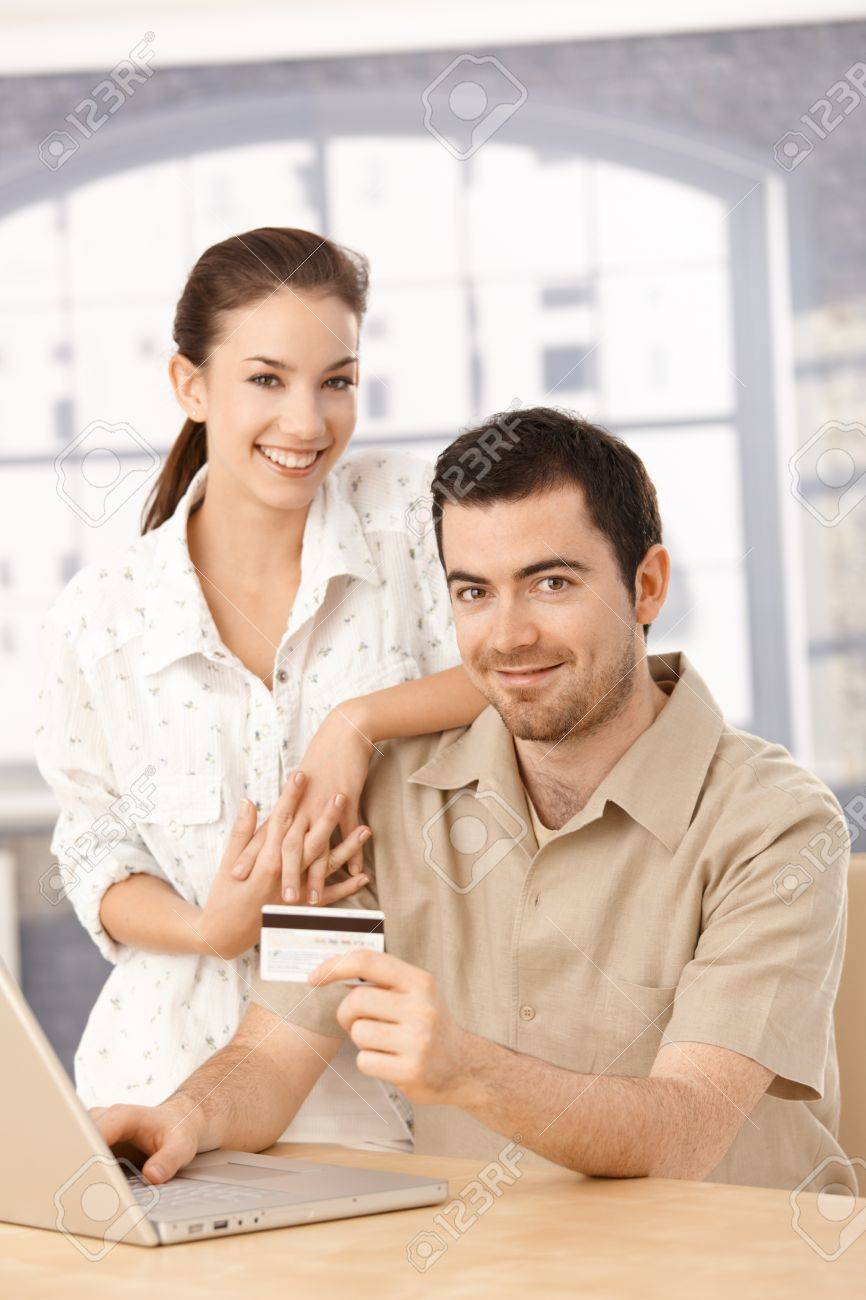 Happy couple using laptop, shopping online at home, using credit card. Stock Photo - 8549473