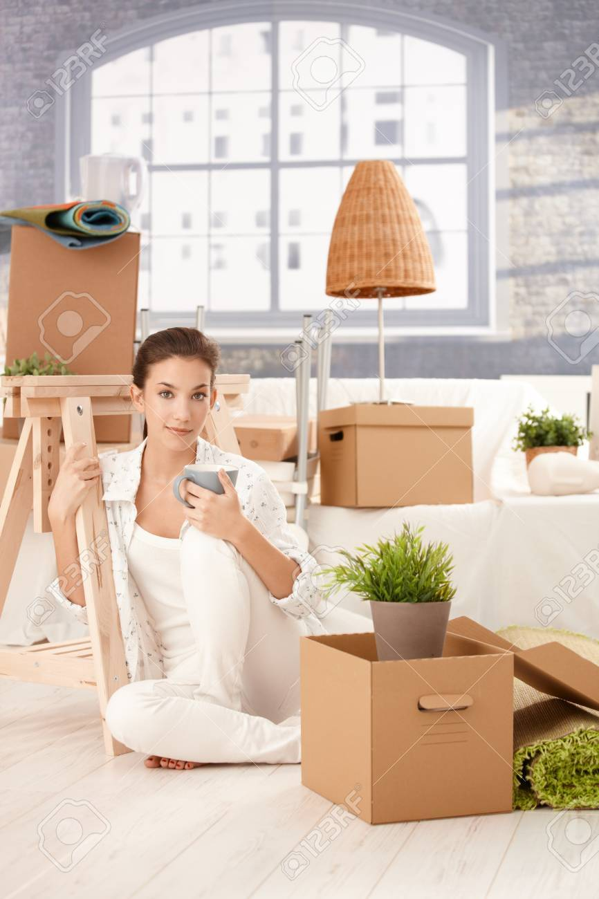 Portrait of young attractive female moving to new house, sitting on floor, drinking tea, boxes around. Stock Photo - 8552011