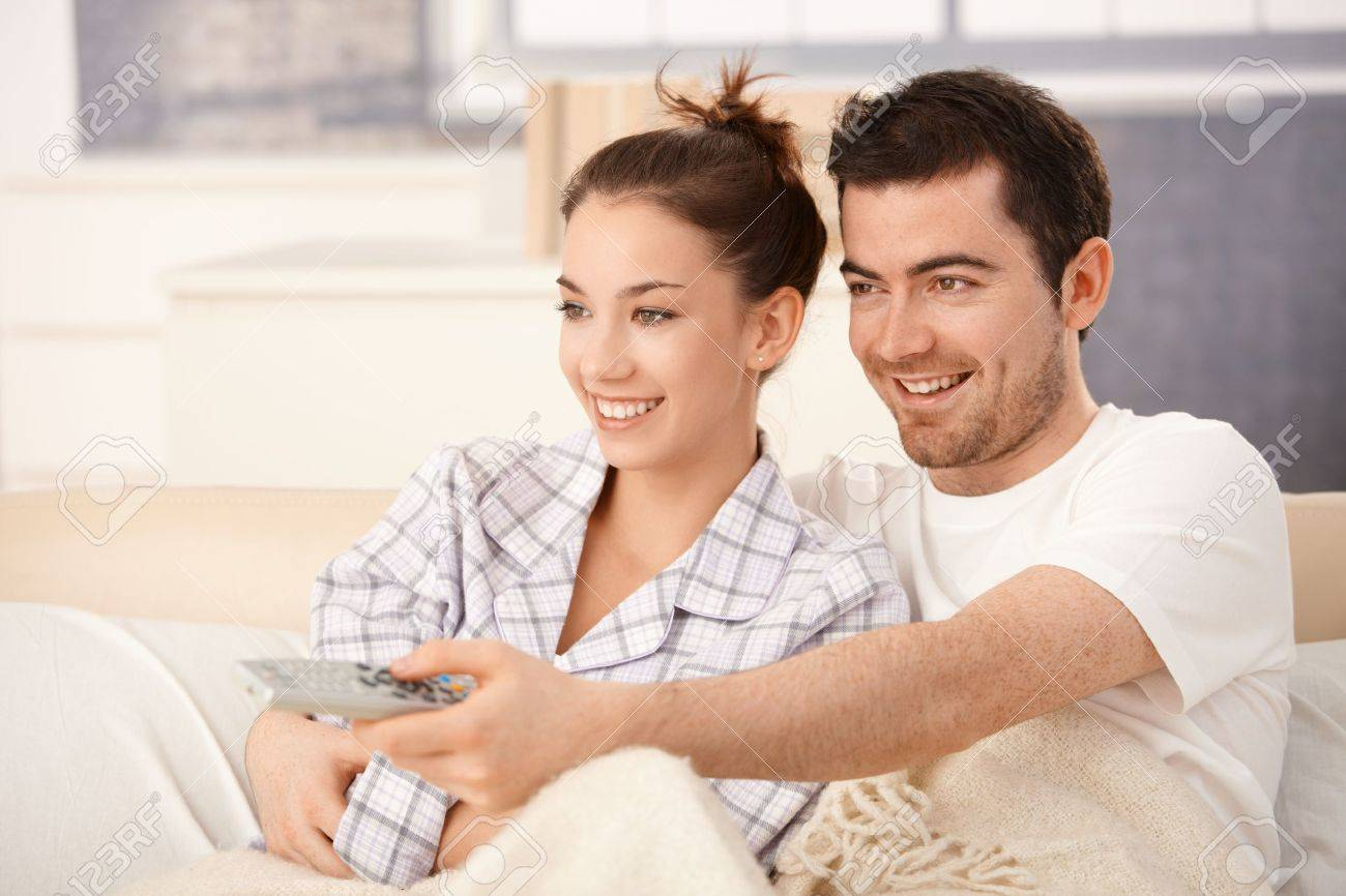 Happy couple watching television in bed, hugging each other, smiling. Stock Photo - 8558324