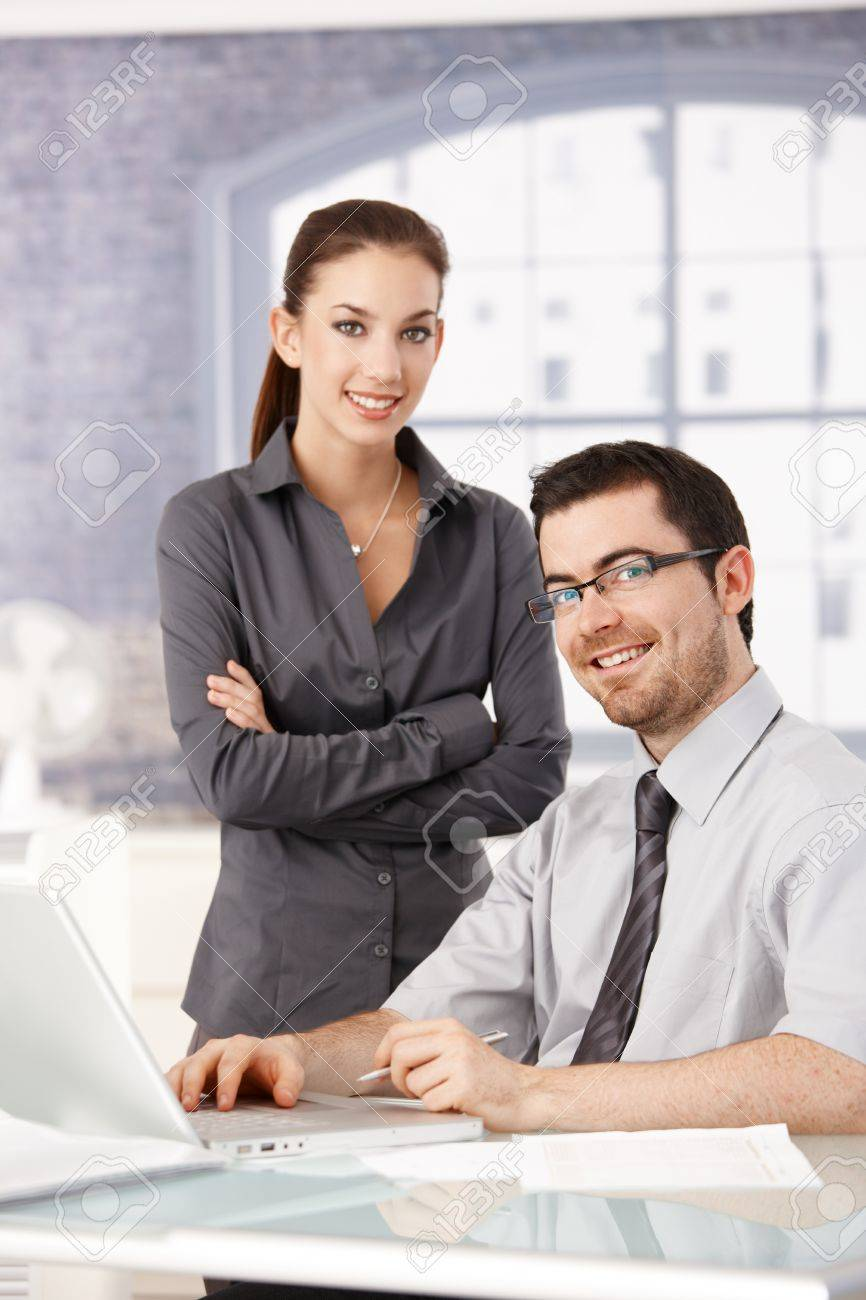 Young colleagues working and smiling in bright office. Stock Photo - 8552015