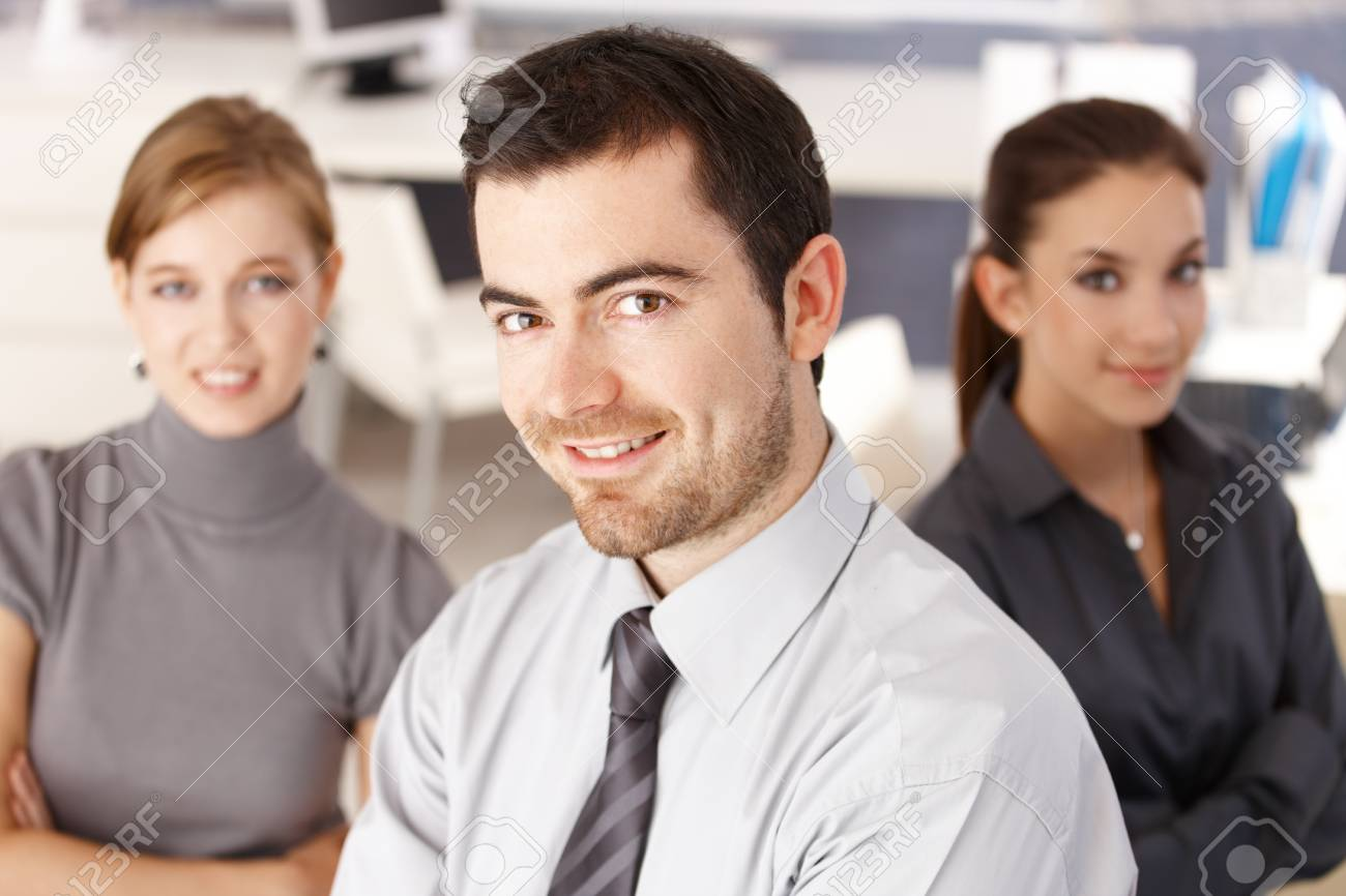 Happy team of young businesspeople smiling in office. Stock Photo - 8549574