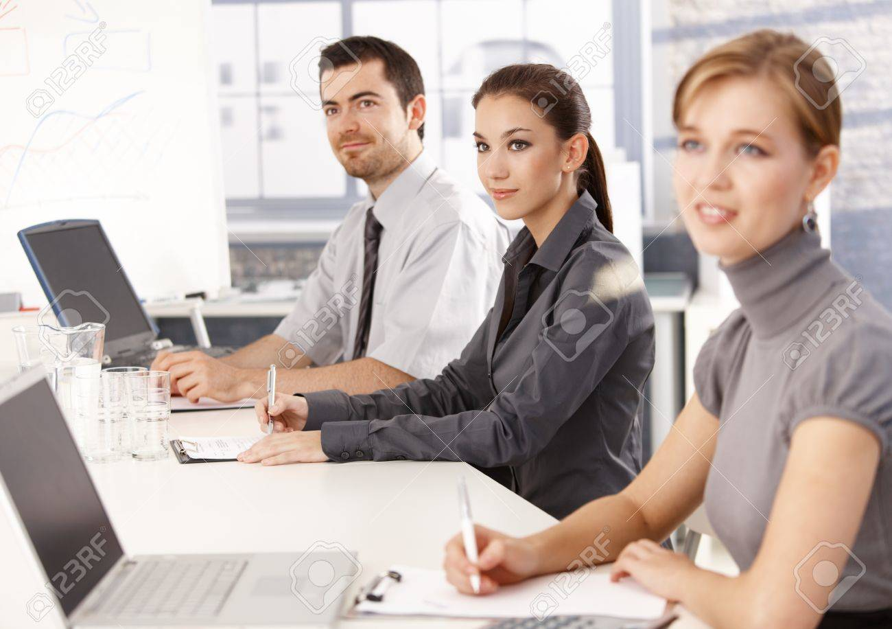 Young businessteam sitting at meeting table, listening presentation, writing notes. Stock Photo - 8556727