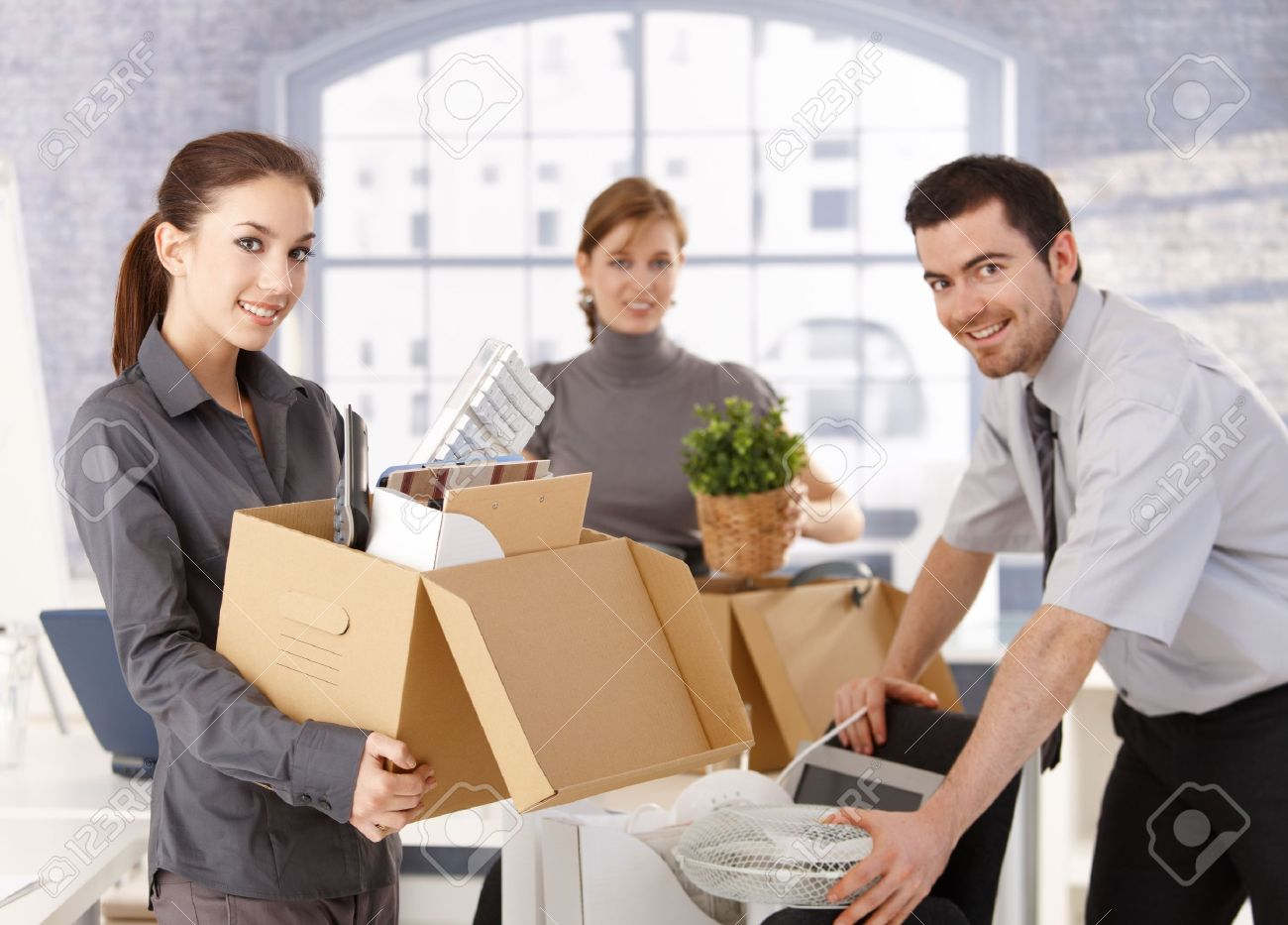Young office workers moving office, unpacking boxes, smiling. Stock Photo - 8551996