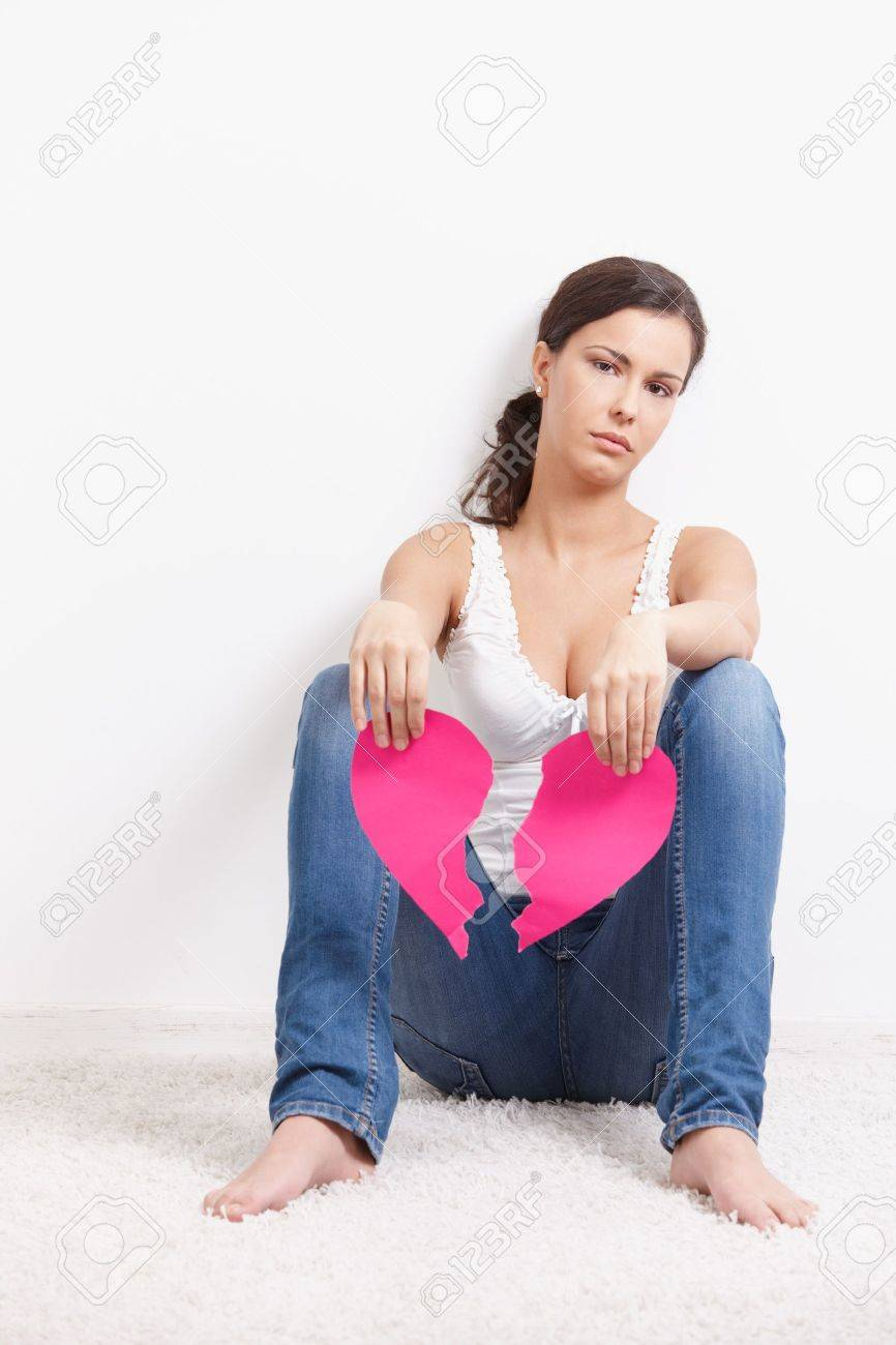 Heart-broken female sitting on floor sadly, holding a torn paper heart in hands. Stock Photo - 8559427