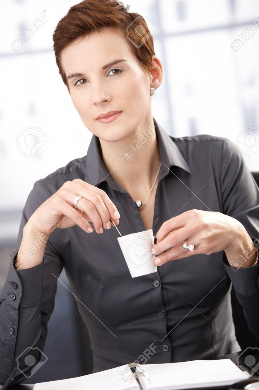 Businesswoman having coffee, with cup handheld, smiling at camera. Stock Photo - 8557570
