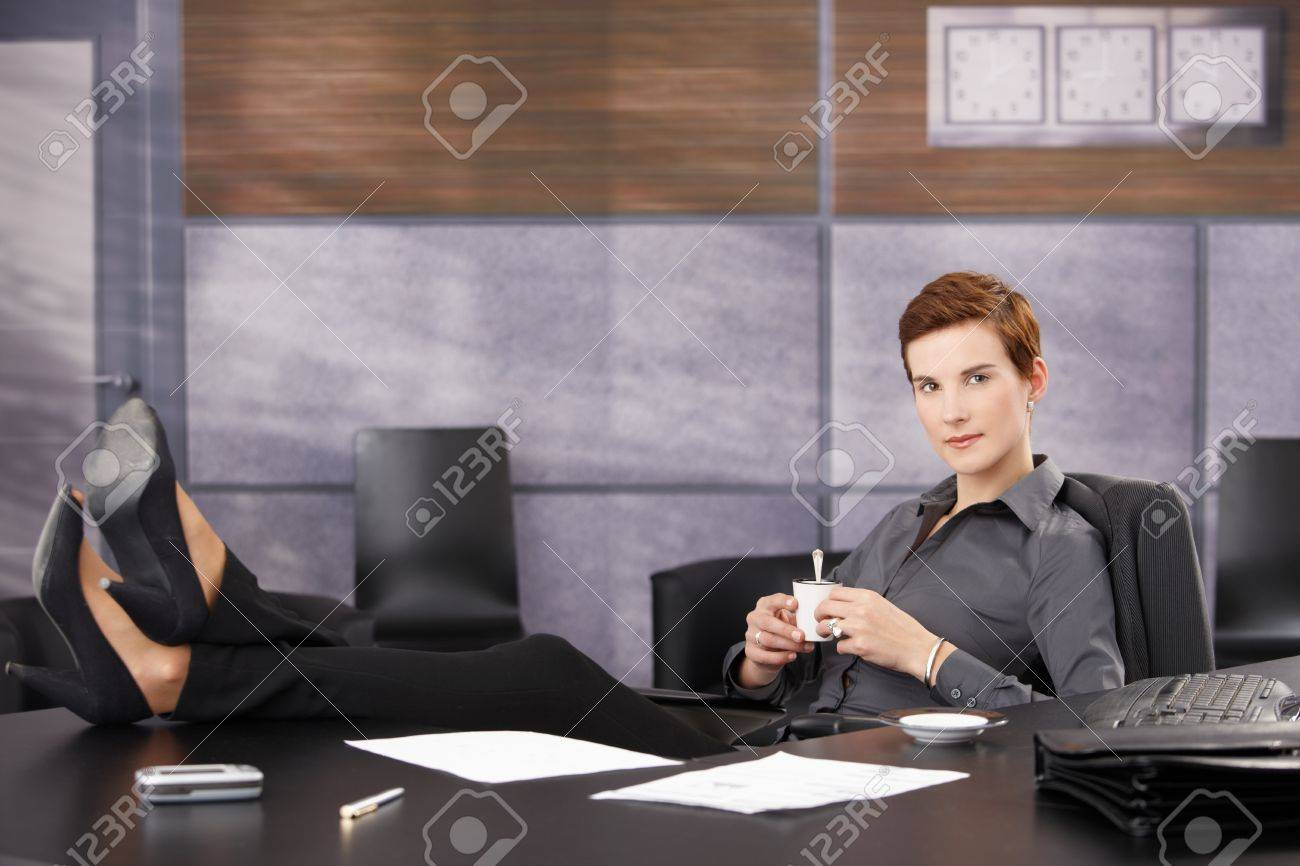Cool businesswoman on coffee break sitting at desk with feet on table, wearing high heels, smiling at camera. Stock Photo - 8553242
