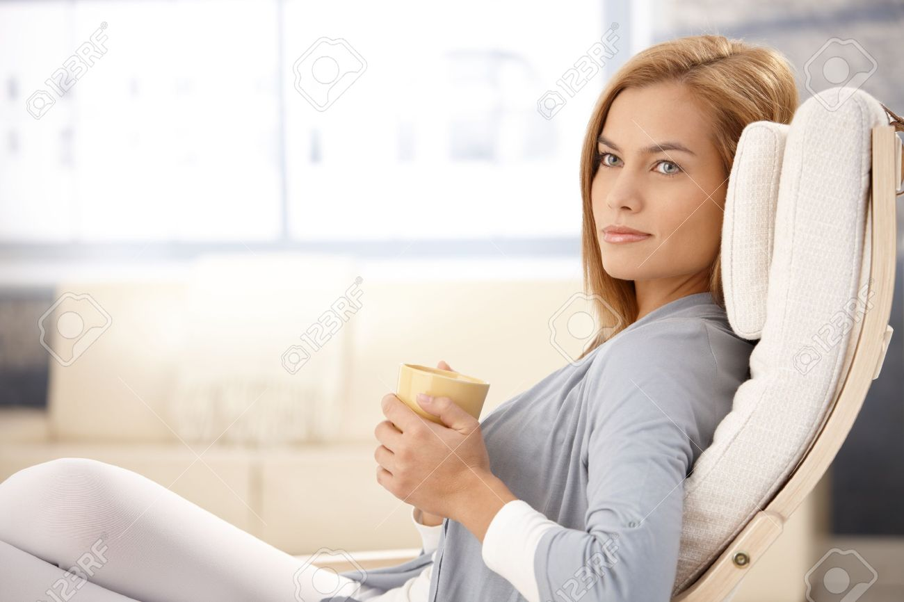 Portrait of beautiful young woman drinking tea in armchair, smiling. Stock Photo - 8586800