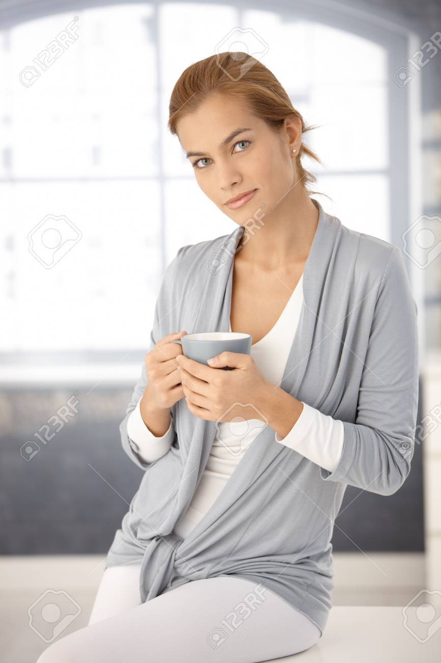 Portrait of pretty woman with tea mug handheld, looking at camera, smiling. Stock Photo - 8586845