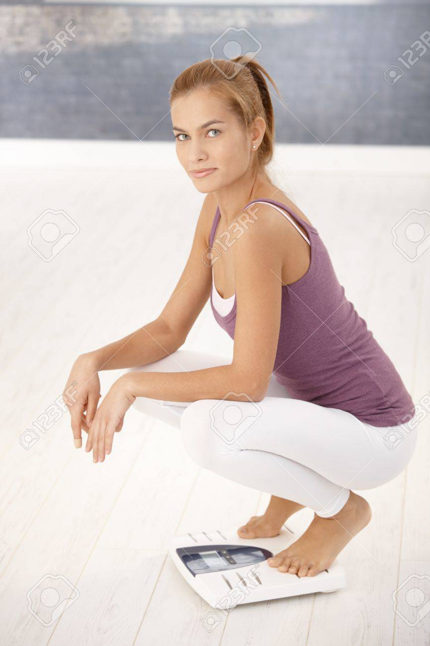 Pretty woman squat on scale, looking at camera, smiling Stock Photo - 8579604