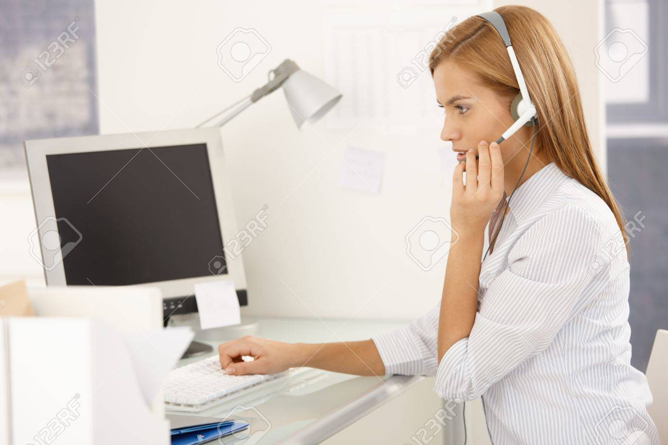 pretty customer service worker girl sitting at desk working pretty customer service worker girl sitting at desk working on computer headset stock