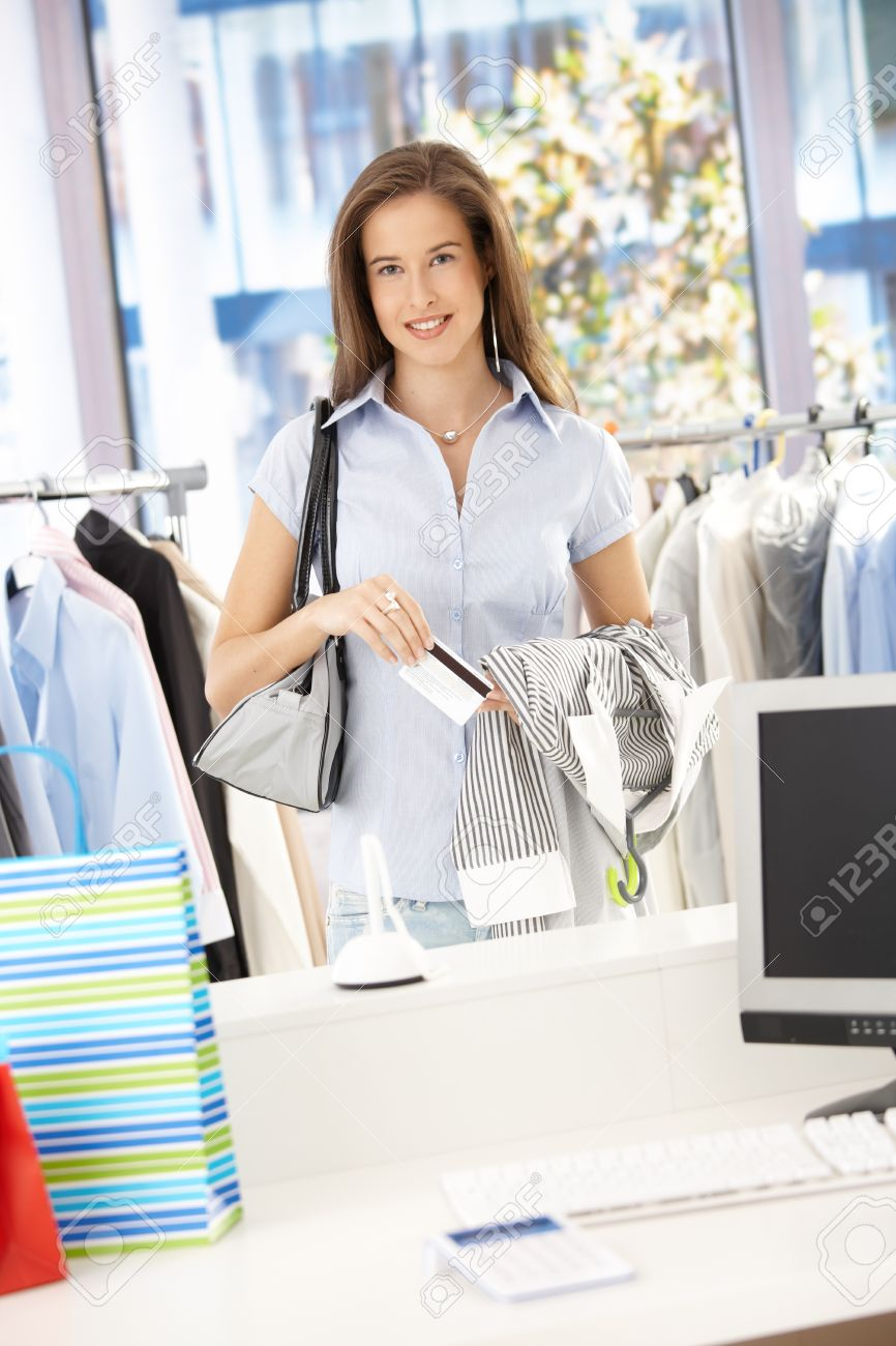 Happy woman paying her shopping with credit card in clothes store, looking at camera, smiling. Stock Photo - 8604165