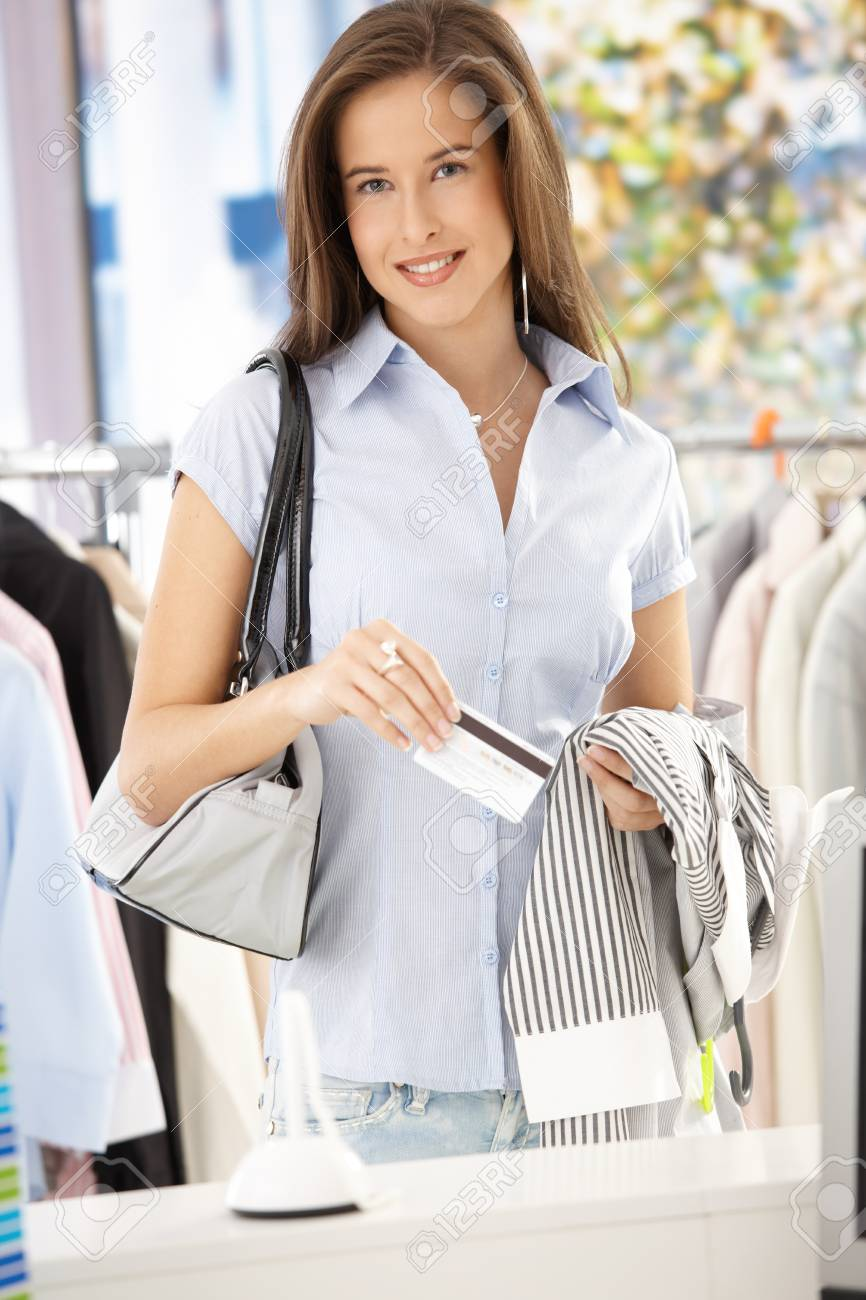 Attractive woman purchasing shirt in clothes store with credit card, smiling at camera. Stock Photo - 8604234