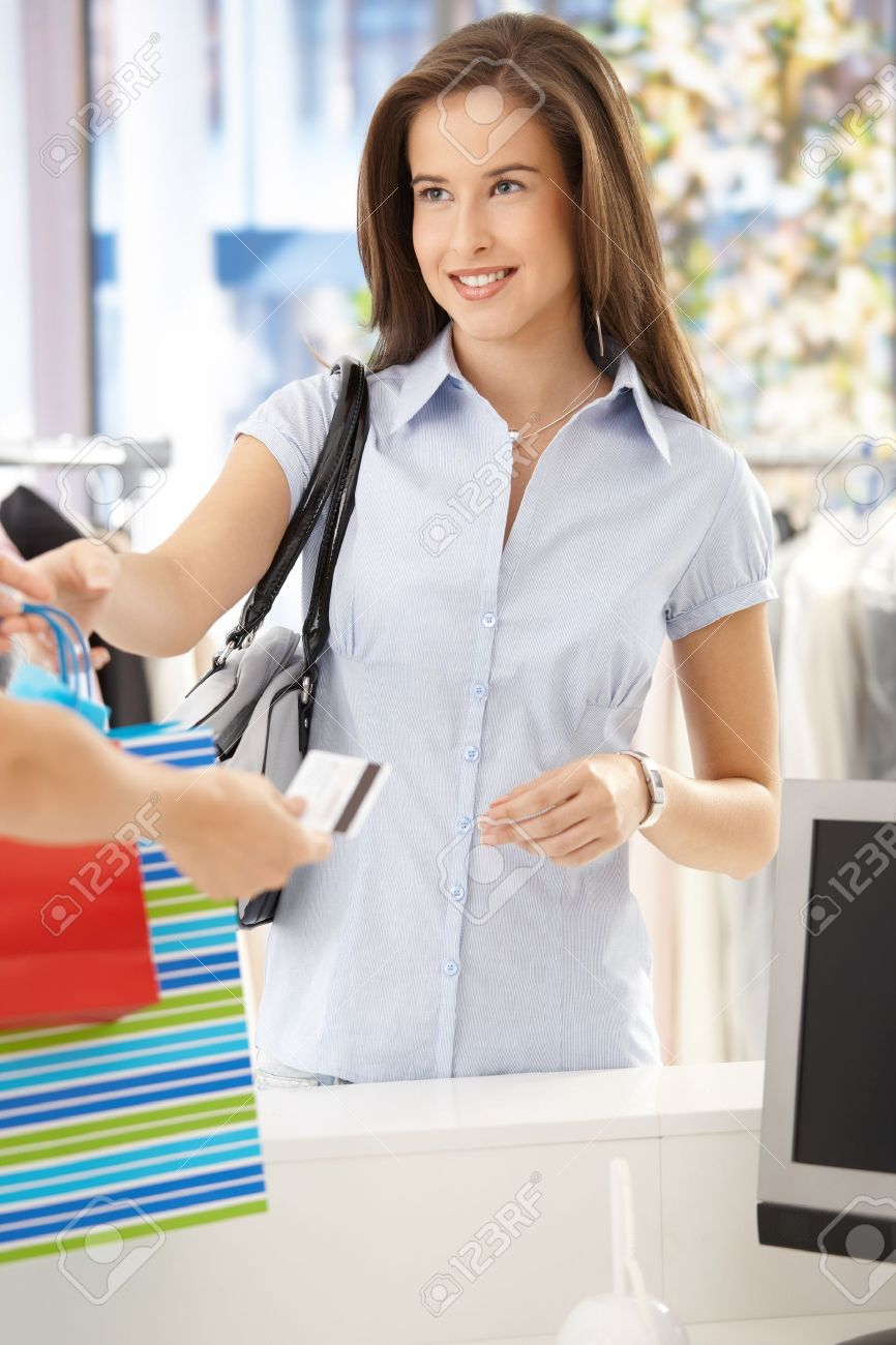 w purchasing clothes in shop getting back credit card stock photo w purchasing clothes in shop getting back credit card smiling at shop assistant