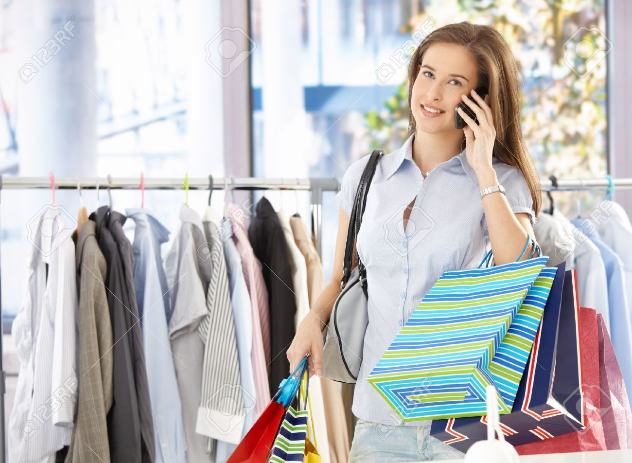 Woman on mobile phone call standing in clothes shop, holding shopping bags, smiling. Stock Photo - 8604176