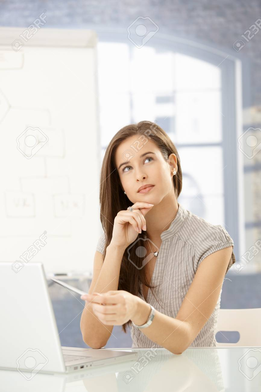 Businesswoman thinking at desk, using laptop computer, concentrating, looking up . Stock Photo - 8604025