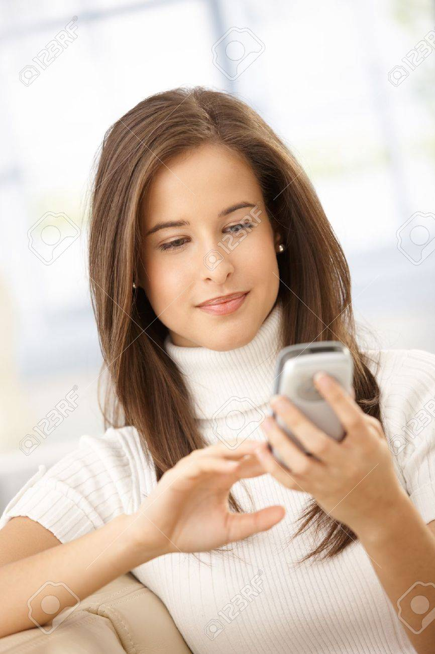 Smiling woman using cellphone handheld, texting, smiling. Stock Photo - 8604131