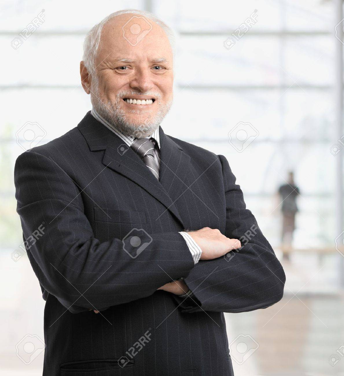 Portrait of successful senior businessman standing in office lobby, smiling. Stock Photo - 8746962