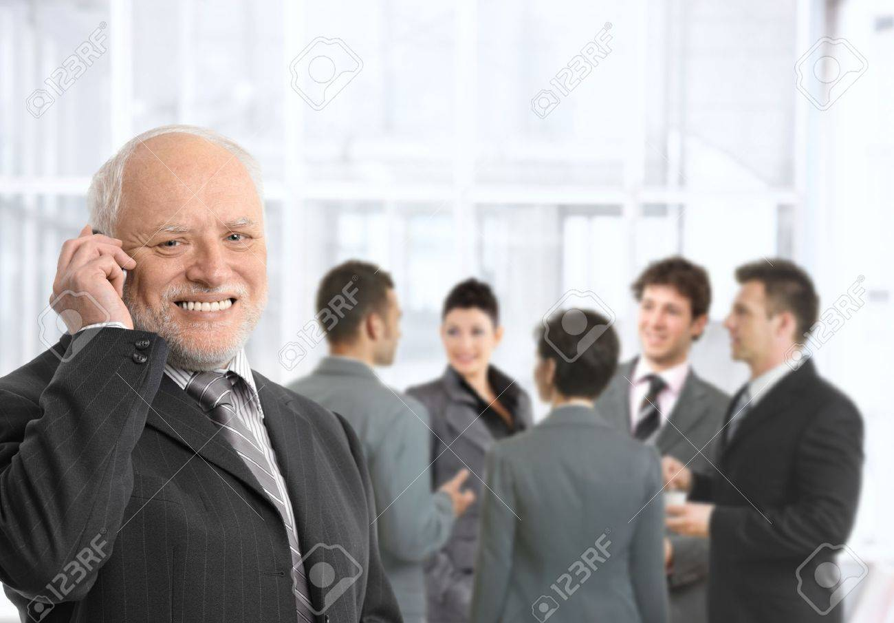 Senior businessman talking on mobile phone in office lobby, smiling, businesspeople chatting in background. Stock Photo - 8746968