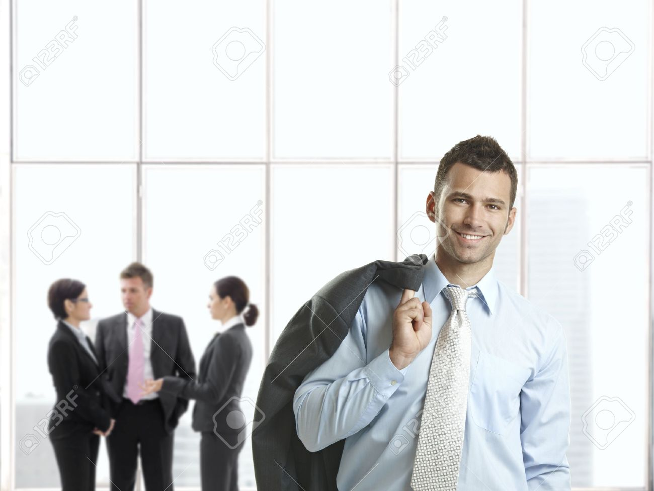 Happy businessman in office lobby smiling at camera, businesspeople talking in background. Stock Photo - 8746933