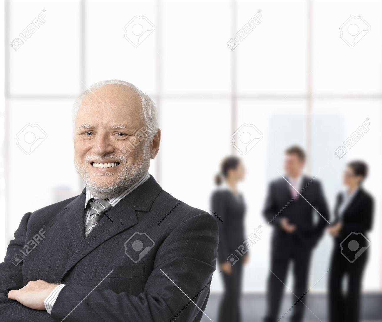 Portrait of smiling senior businessman standing with arms folded, businesspeople in background. Stock Photo - 8746945