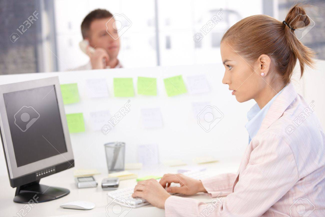 Young woman sitting at desk, working on computer, busy. Stock Photo - 8747029