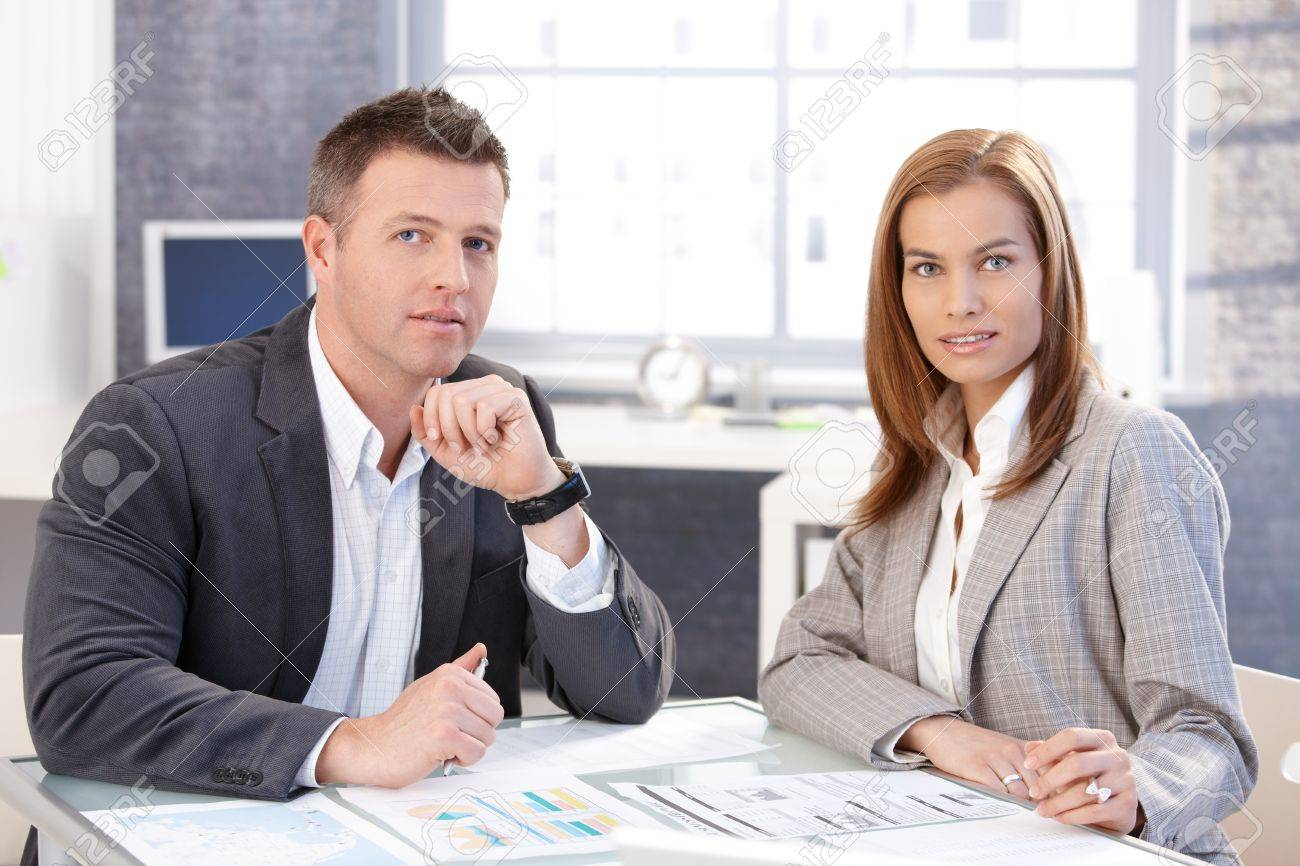 Attractive young businesspeople working together, sitting at desk in bright office, smiling. Stock Photo - 8747146