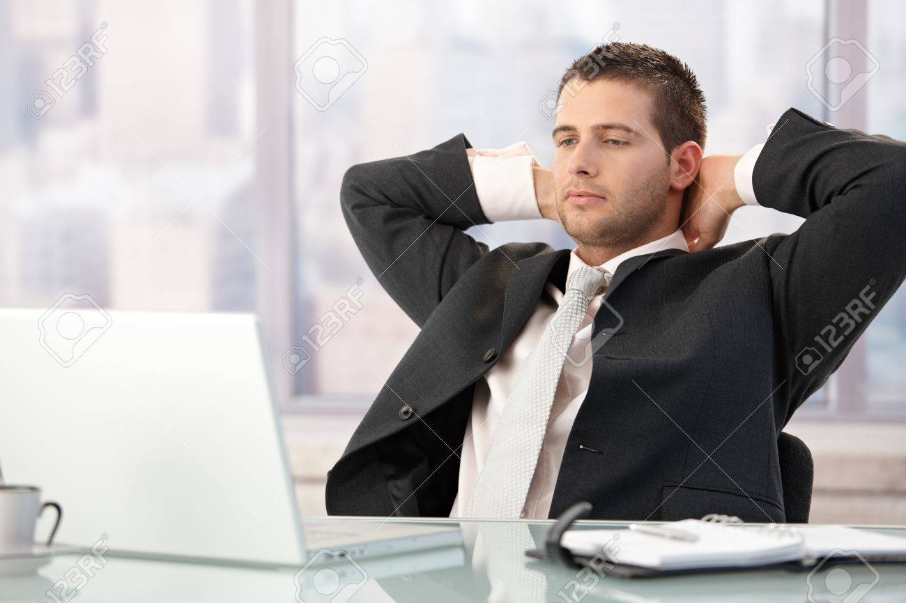 Handsome executive sitting at desk in bright office, stretching. Stock Photo - 8747333