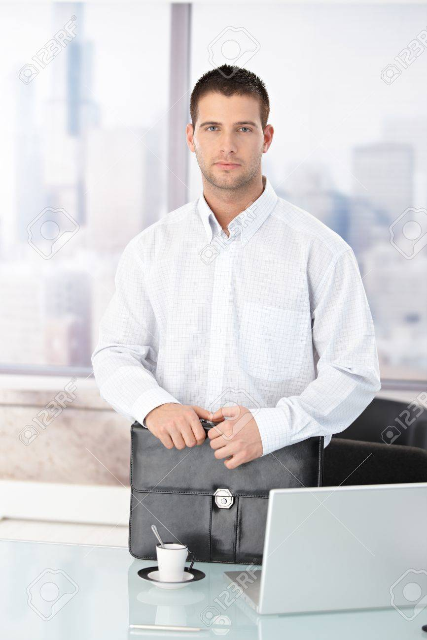 Casual office worker standing in bright office, having briefcase. Stock Photo - 8747316