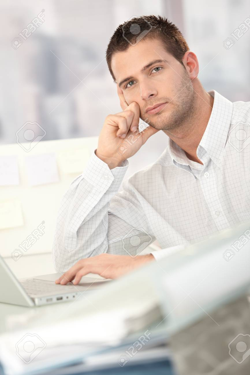 Troubled businessman sitting at desk in office. Stock Photo - 8747323
