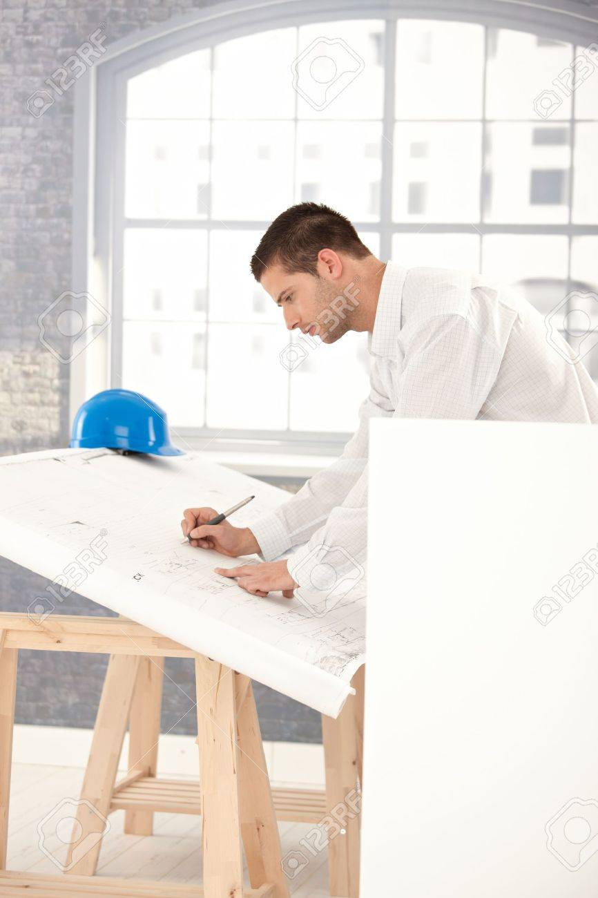 Handsome young architect drawing plans in office. Stock Photo - 8747174