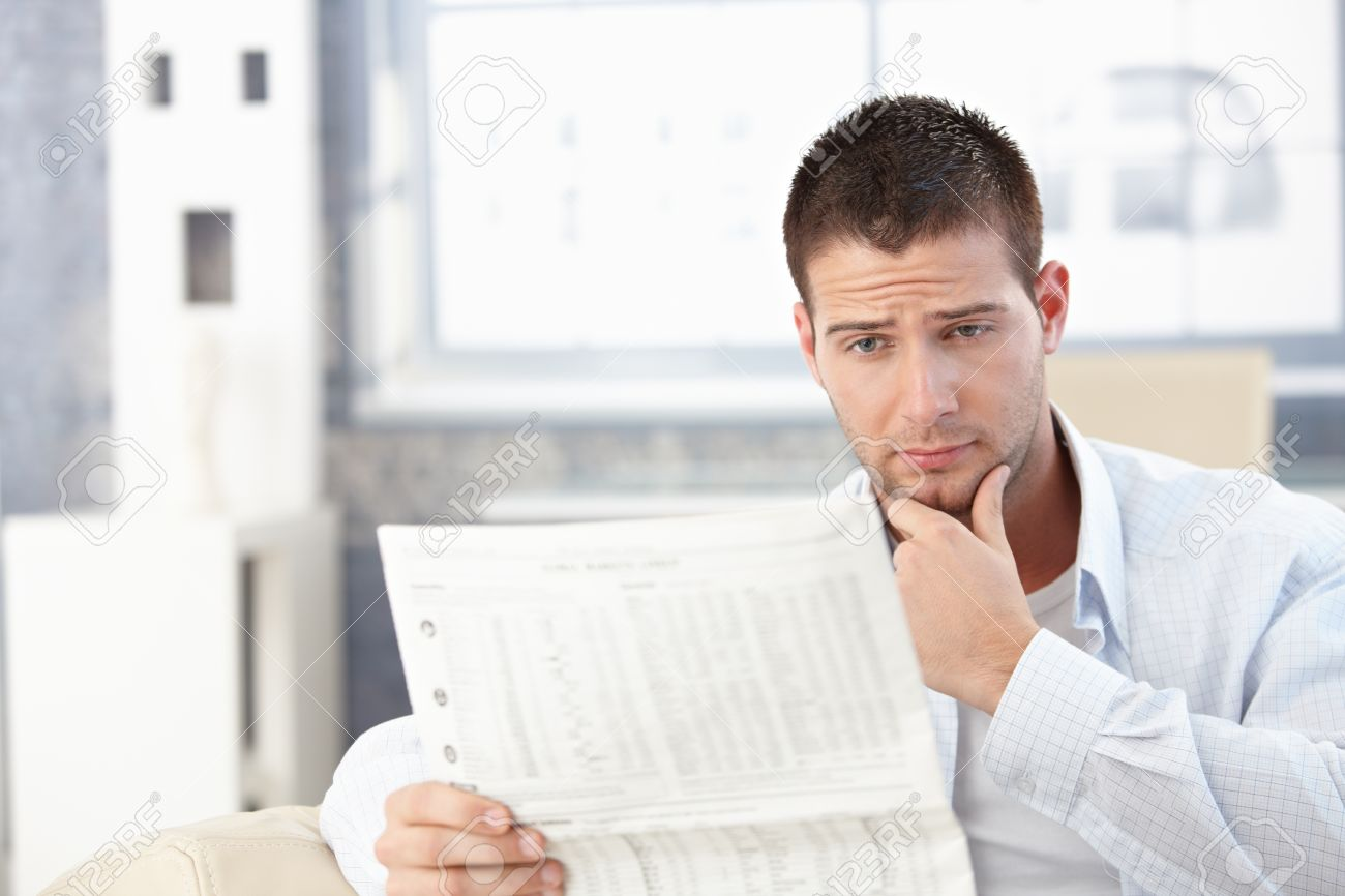 young man reading newspaper at home, looking worried. stock photo