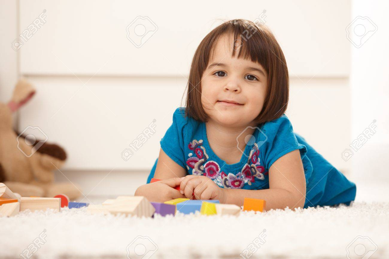 Portrait of cute little girl playing on floor, smiling at camera. Stock Photo - 8747432