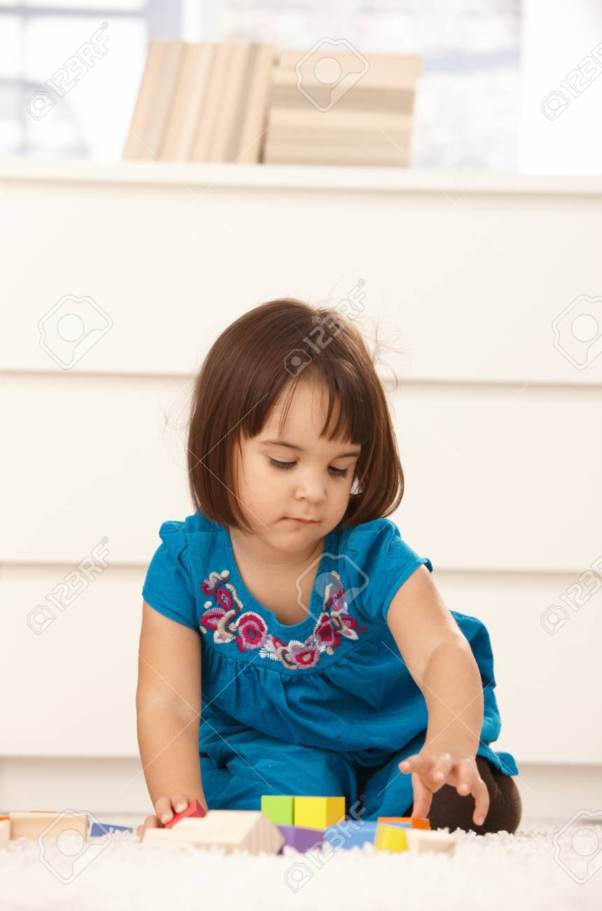 Small girl playing with building block at home, on floor, concentrating. Stock Photo - 8747437