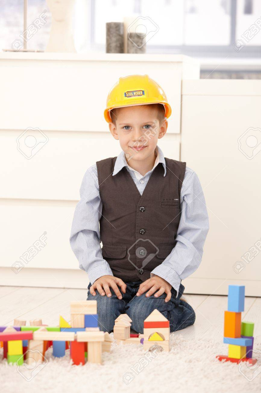 Portrait of smiling young boy kneeling in builder hat playing with building block set. Stock Photo - 8747442
