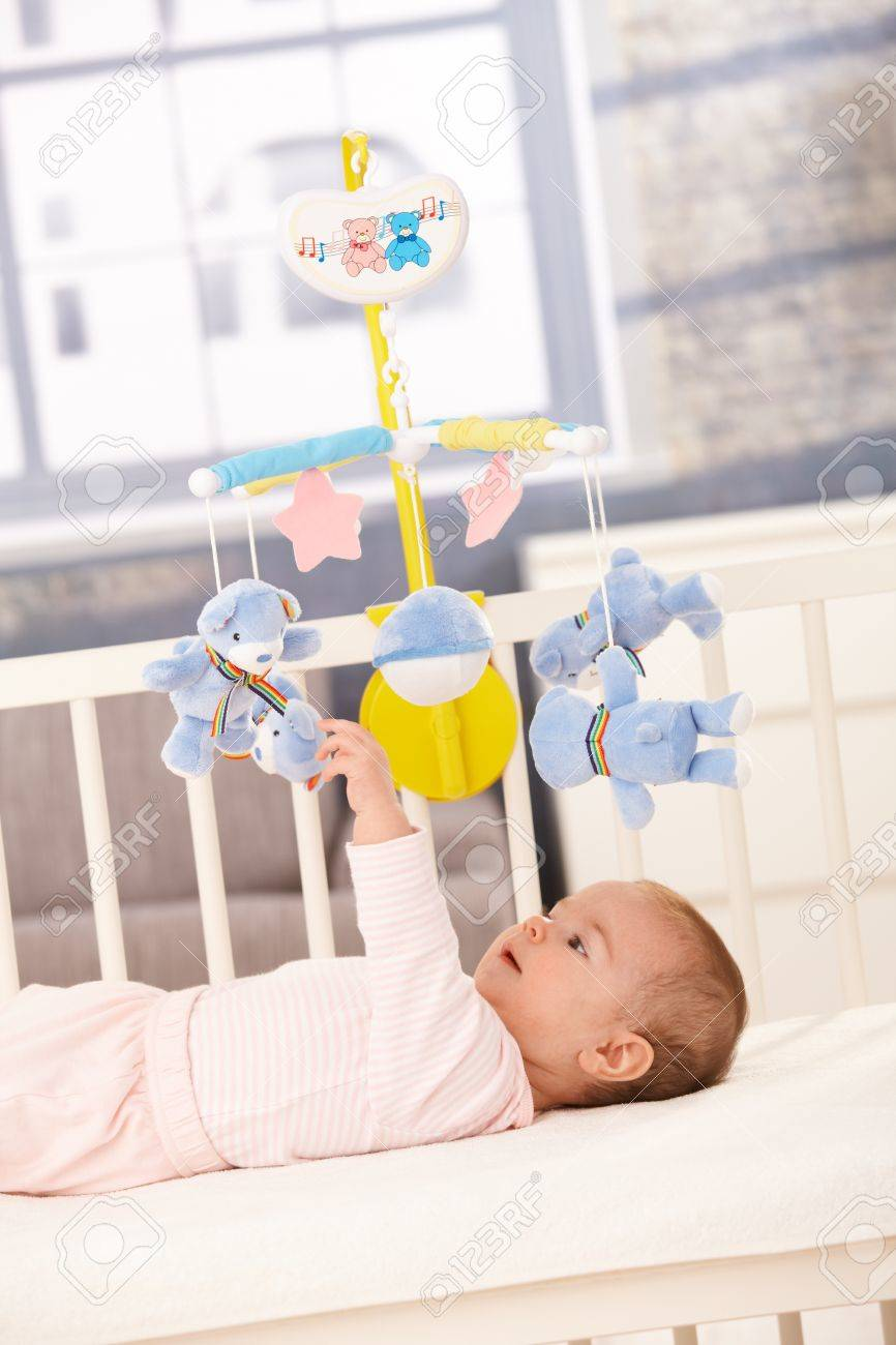 Baby bed mobile - Baby Playing With Bed Mobile Toy Reaching Up To Teddy Bear Stock Photo